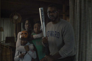 Us 2019 Movie Scene Winston Duke holding a baseball bat with the rest of the family behind him as they first see the strangers