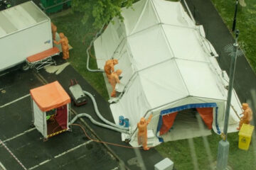 Containment 2015 Movie Scene People in orange hazmat suits setting up tents outside the apartment building