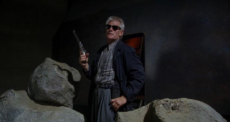 Dollman 1991 Movie Scene Tim Thomerson as Brick Bardo in front of his spaceship holding a huge gun
