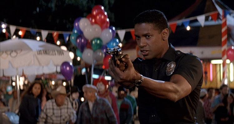 Ricochet 1991 Movie Scene Denzel Washington as Nick Styles holding a gun in a police uniform at the fair