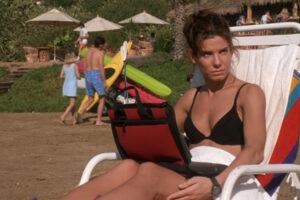 The Net 1995 Movie Scene Sandra Bullock as Angela Bennett in a swimsuit working on her laptop on the beach
