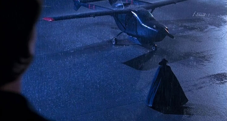 The Night Flier 1997 Movie Scene Michael H. Moss as Dwight Renfield walking towards his black Cessna Skymaster wearing a large cape in the rain