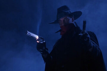 The Shadow 1994 Movie Scene Alec Baldwin as Lamont Cranston AKA The Shadow holding two guns with a hat and red bandana on the bridge
