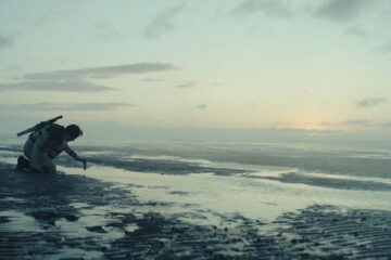Tides 2021 Movie Scene Nora Arnezeder as Blake taking samples at the beach