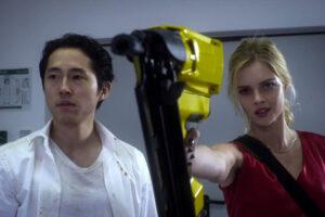 Mayhem 2017 Movie Scene Steven Yeun as Derek Cho and Samara Weaving as Melanie Cross holding a nailgun