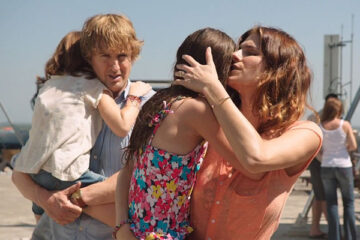 No Escape 2015 Movie Scene Lake Bell as Annie Dwyer and Owen Wilson as Jack Dwyer holding their daughters on the rooftop of hotel