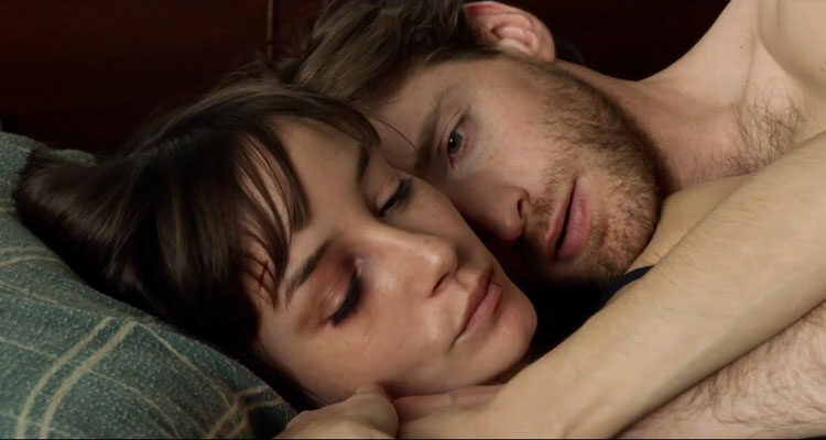 The Living 2014 Movie Scene Fran Kranz as Teddy and Jocelin Donahue as Molly laying in bed