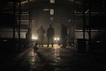The Standoff at Sparrow Creek 2018 Movie Scene Members of the militia standing in the dark and questioning Robert Aramayo as Keating