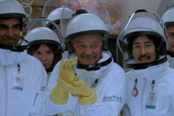 Warning Sign 1985 Movie Scene Richard Dysart as Dr. Nielsen holding a vial and posing for a picture with the rest of the scientist in a laboratory