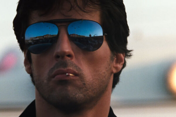 Cobra 1986 Movie Scene Sylvester Stallone as Marion Cobretti wearing sunglasses and playing with a matchstick in the corner of his mouth