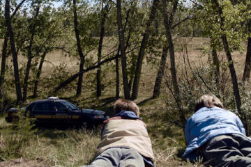 Cop Car 2015 Movie Scene Hays Wellford as Harrison and James Freedson-Jackson as Travis looking at an abandoned police car