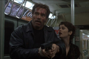 End Of Days 1999 Movie Scene Arnold Schwarzenegger as Jericho and Robin Tunney as Christine holding a gun in subway