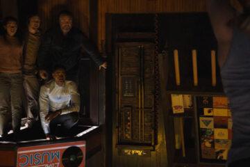 Escape Room 2019 Movie Scene Taylor Russell as Zoey Davis, Tyler Labine as Mike Nolan, Jay Ellis as Jason Walker and Logan Miller as Ben Miller in the upside down bar