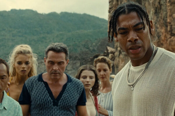 Old 2021 Movie Scene Aaron Pierre as Mid-Sized Sedan, Rufus Sewell as Charles, Ken Leung as Jarin, Abbey Lee as Chrystal, Vicky Krieps as Prisca and Thomasin McKenzie as Maddox looking at a corpse at the beach