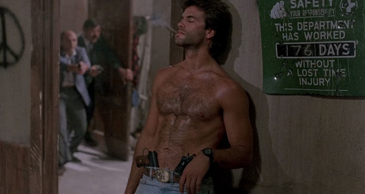 Snake Eater 1989 Movie Scene Lorenzo Lamas as Jack Soldier Kelly without a shirt, smoking a cigar with two guns in his jeans