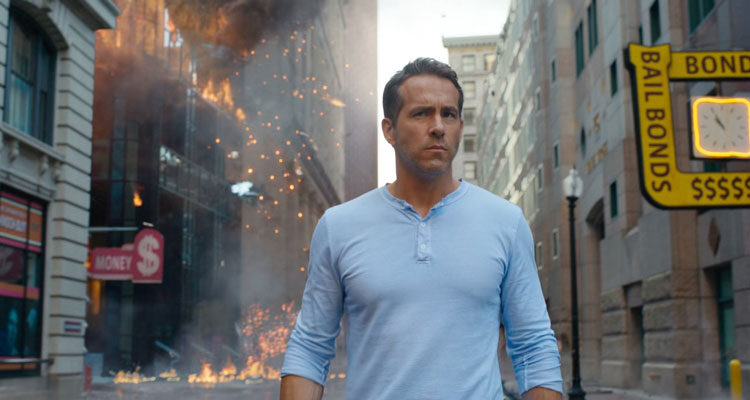 Free Guy 2021 Movie Scene Ryan Reynolds as Guy wearing a blue shirt with a building exploding behind him