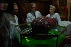 The Brain 1988 Movie Scene Christine Kossak as Vivian, David Gale as Dr. Anthony Blakely and George Buza as Verna looking at a giant brain in green liquid